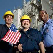 Workers wearing hardhats and holding USA flag